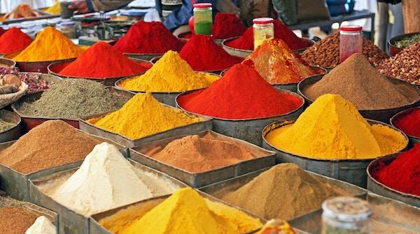 En krydderleverandør på et lokalt marked i Marokko: fargerike, pulveriserte krydder i store gryter, Afrika.