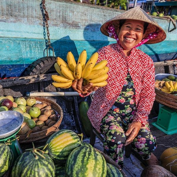 Vietnamesisk kvvinne som selger bananer på et flytende marked, Mekong-elven, Vietnam