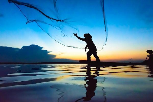 En fisker i aksjon under solnedgang
