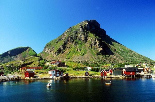 Øya Lovund på Helgelandskysten med røde hus og fjell i bakgrunnen og båter på sjøen