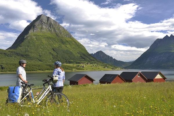 To personer på sykkeltur parkerte sykler med fjell og natur i bakgrunn