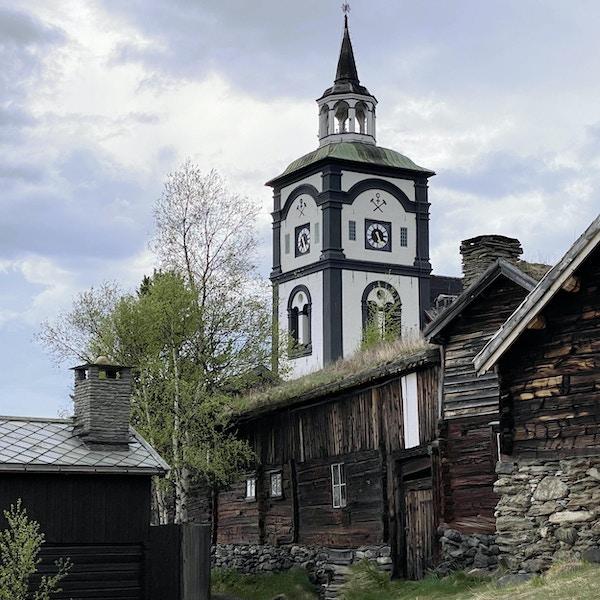 Kirketårn i svart og hvitt, med tradisjonelt gårdstun i forkant.