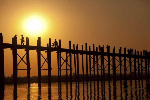 U Bein-broen ved solnedgang med mennesker som krysser elven Ayeyarwady, Mandalay, Myanmar