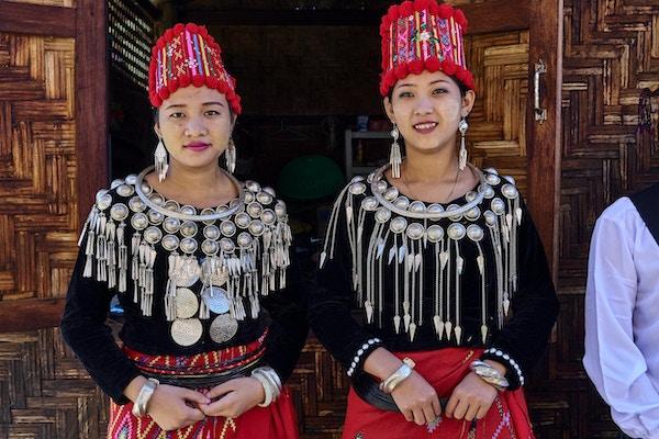 To lokale damer i tradisjonelle kostymer med sølv og røde farger. Foto.