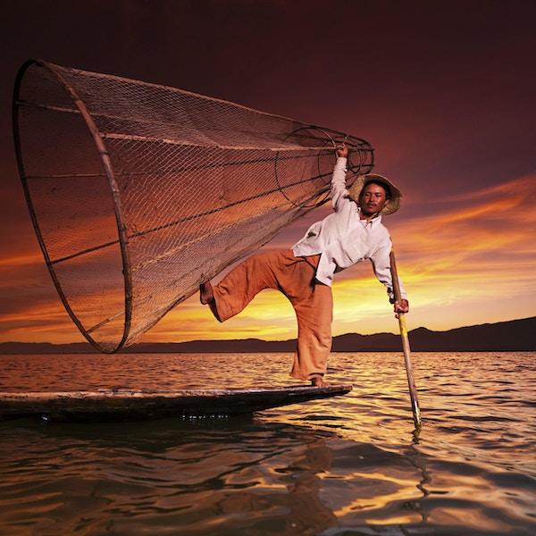 En fisker på Inle Lake i vakker solnedgang. Ben-roende fiskere på Inle Lake er et viktig turistmål i Myanmar (Burma).