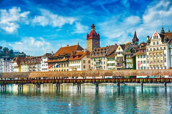 Vakkert bybilde av gamlebyen i Lucerne, synlig er elven Reuss strandpromenade i Lucerne med den berømte Kapellbrucke-broen som opprinnelig ble bygget i 1333, tradisjonelle sveitsiske bygninger, kirker, restauranter, kaffebarer, hoteller, vakkert skyer og refleksjon i vannet.