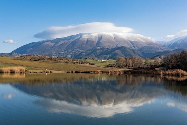 Blank innsjø i forgrunnen, med høyt fjell i bakgrunnen. Foto.