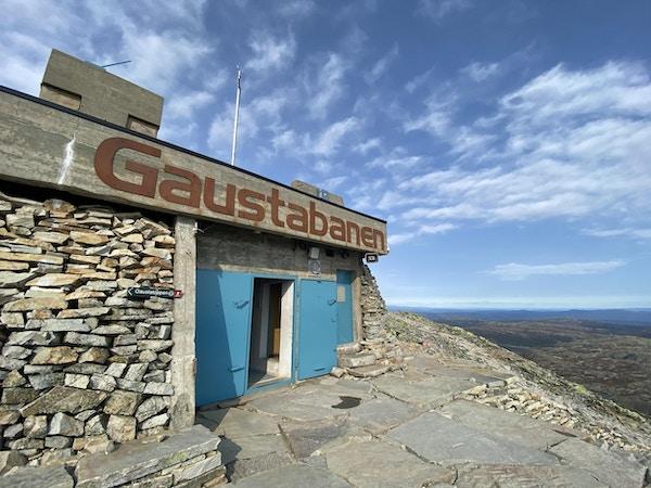 Skilt med Gaustabanen over blå dør og på toppen av fjellet