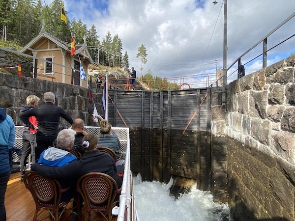 Personer om bord i båt på kanal som sitter og venter på slusepassering