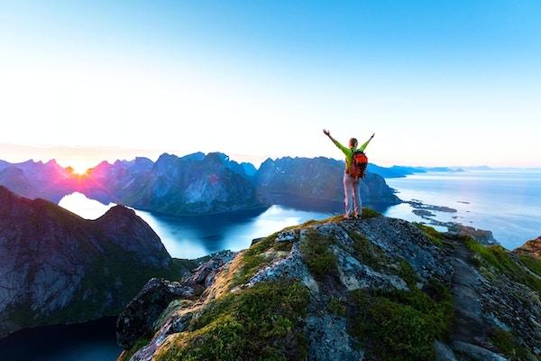 Glad kvinne, turgåer, nytelse, naturskjønn utsikt, av, midnattssol, på, det, topp, av, Reinebringen, fottur, over, reine, landsby, inn, det, lofoten, skjærgård, i løpet av, arktisk, sommer, norge