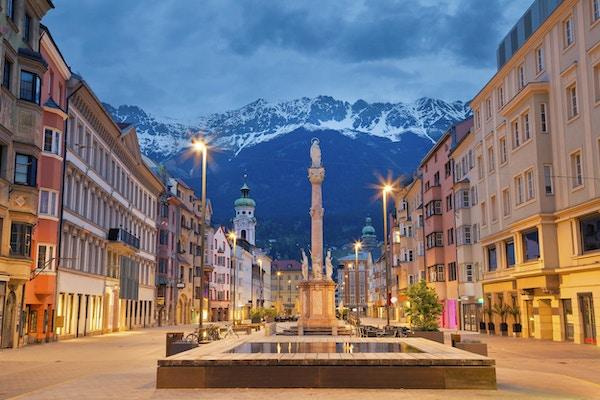 Bilde av Innsbruck, Østerrike i skumring med alpenbe i bakgrunnen.