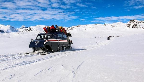 Beltebil med bagasje på taket i vinterlandskap.