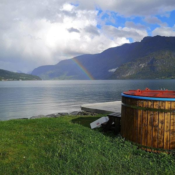 Badestamp ved fjorden med regnbue i bakgrunnen.