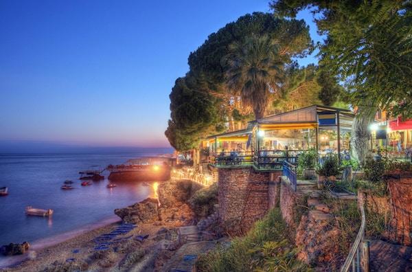 Restauranter og hotell ved stranden i landsbyen Dhermia, som ligger i den albanske Riveria på den joniske kysten. Liten uskarphet av båter, mennesker og trær på grunn av flere lange eksponeringer som trengs for behandling av høyt dynamisk område.