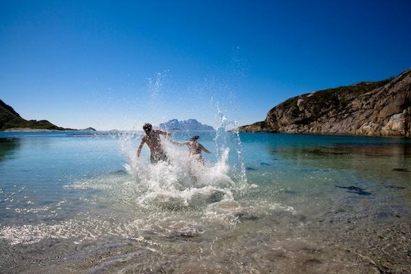 To mennesker løper ut i havet på fin sandstrand om sommeren.