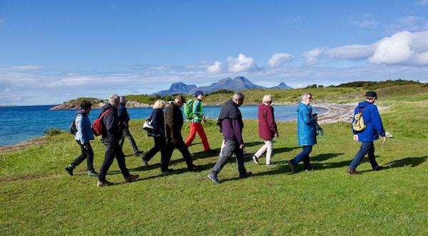 Mennesker på kystvandring langs fjæra over kritthvite strender utenfor Bodø