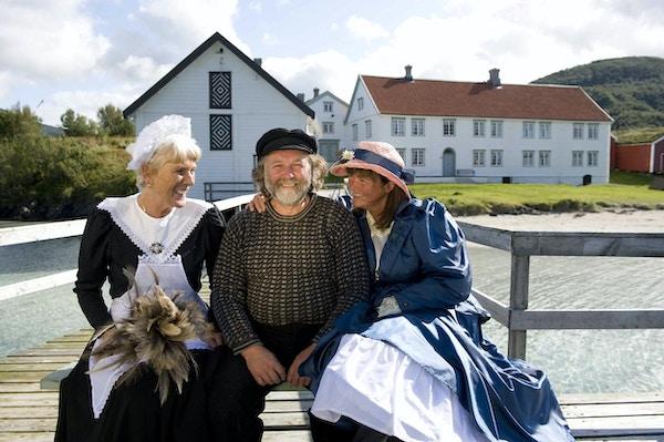 Mann og to kvinner kledd i gammeldagse kjær sittende på brygga med historiske bygninger i bakgrunnen.