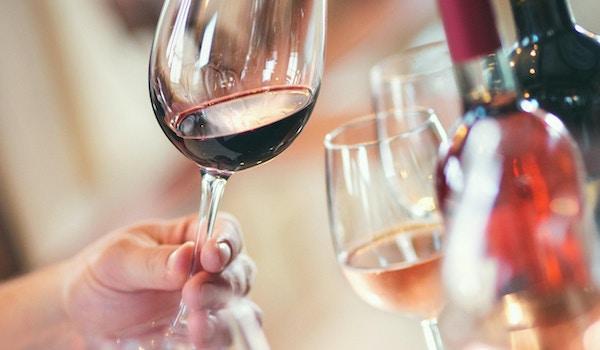 Nærbilde av ugjenkjennelige voksne som holder glass vin og utfører visuell undersøkelse. Evaluering av utseende, farge, klarhet, rester på glasset. Det er vinflasker og andre vinprøver i bakgrunnen.