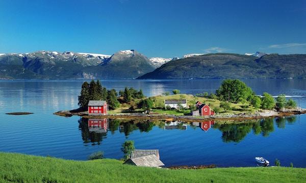 Hardangerfjord på Sør-Vestlandet om sommeren. Et rødt, norsk hus som ligger på en liten øy i fjorden. I det fjerne Folgefonna-breen. Bildet ble tatt i nærheten av landsbyen Omastranda.