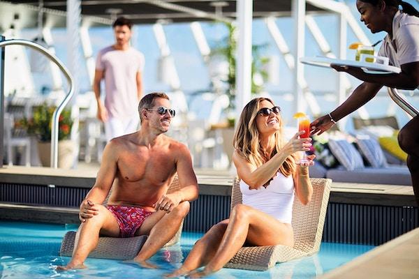 Par som enjouing en fargerik drink i bassenget