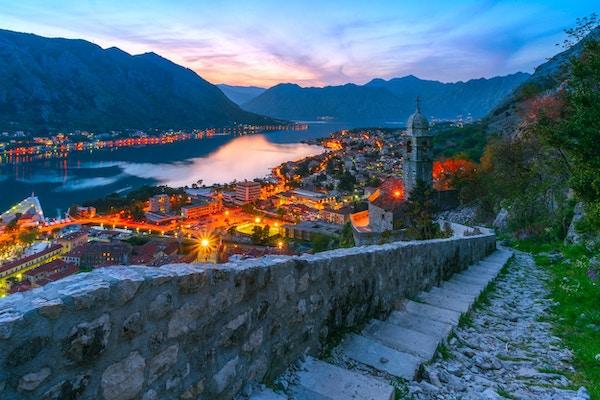 Utsikt fra bakken til Adriaterhavsbyen og den pittoreske bukten om kvelden, natten. Byen på fjellet. Natt bylys. Den gamle montenegrinske byen Kotor.