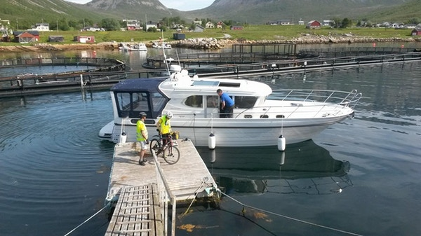 To syklister på vei ombord på en båt.