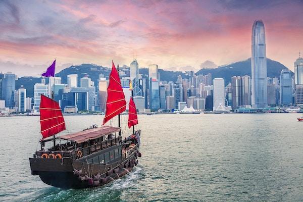Seilbåt seiler inn til Hong Kong Victoria Harbour ved solnedgang