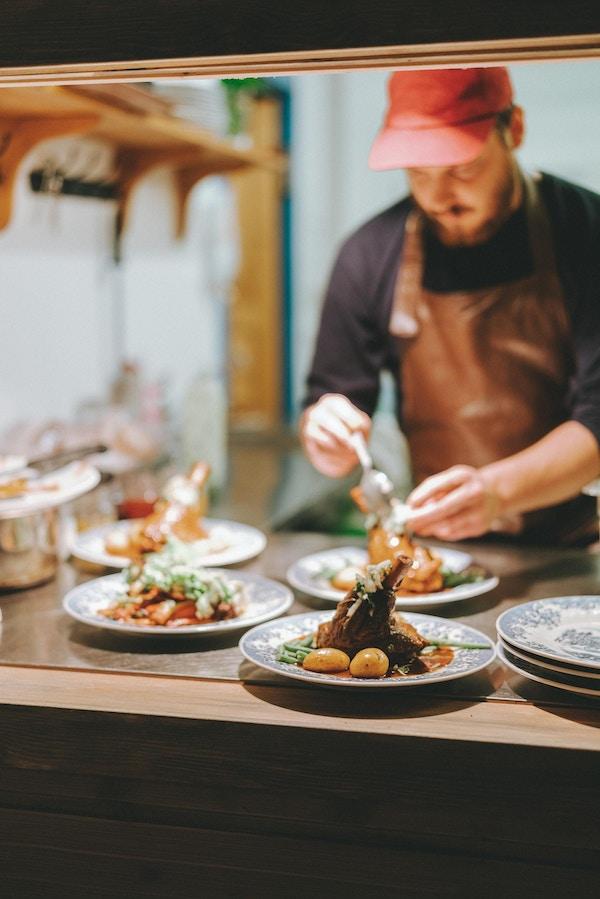 Kokk danderer middagstallerkener ved Skårungen.