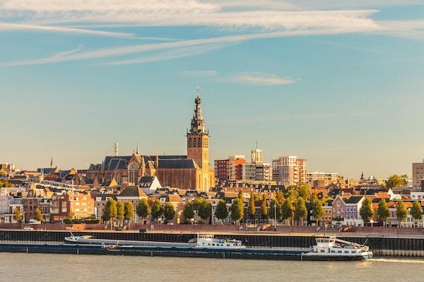 Den nederlandske byen Nijmegen under solnedgang med elven Waal foran