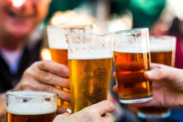 Nærbilde fargebilde som viser en gruppe mennesker som feirer med en skål. Folket jubler glassene sine øl (halvliter øl) sammen i en gest av feiring, samvær og lykke. Folket er fokusert i bakgrunnen, mens fokuset er på ølglassene i forgrunnen. Rom for kopiplass.
