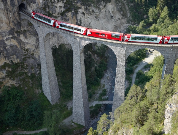 Glacier Express kjører over en høy bro inn i en tunnell.