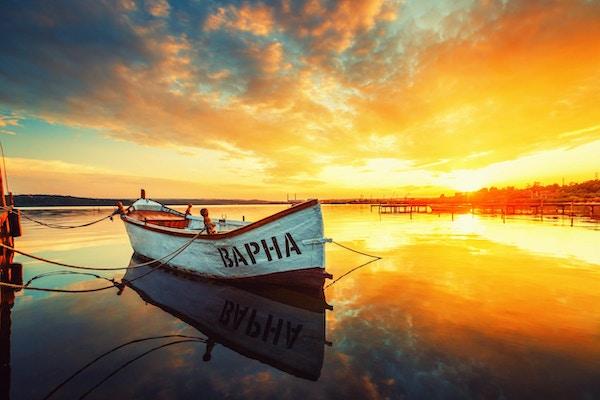 Fiskebåt på Varna innsjø med refleksjon i vannet ved solnedgang.