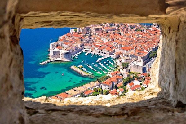 Dubrovnik historiske by- og havneutsikt gjennom steinvinduet fra Srd-bakken, Dalmatia-regionen i Kroatia