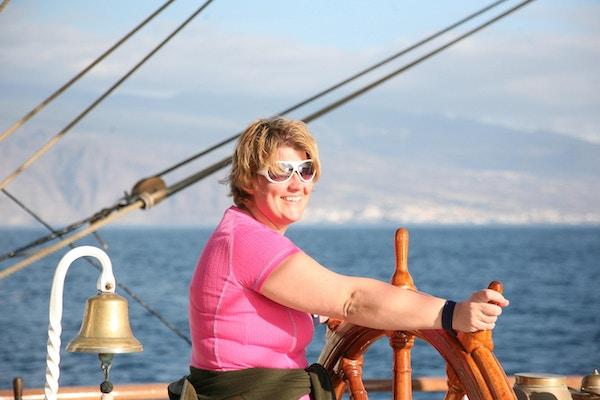 Kvinne som står ved skipsrattet