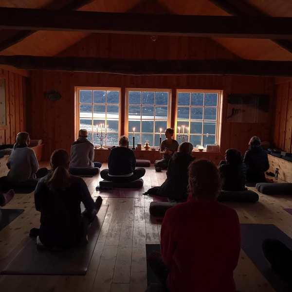 Folk gjør yoga i trehus ved fjorden.