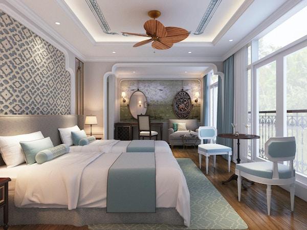 Lugar med seng, sittegruppe, speil, vinduer, takvifte og fransk balkong. Foto.