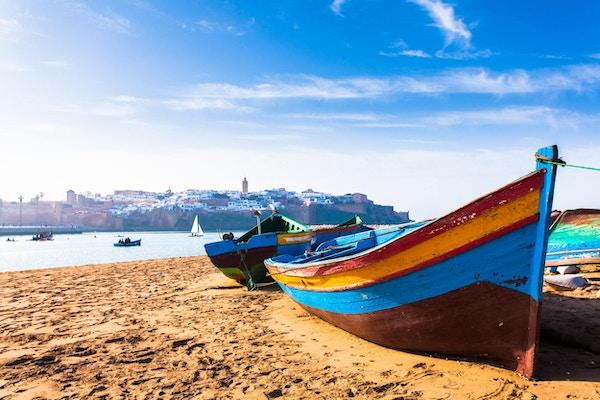 Båter langs stranden og medinaen i bakgrunnen.