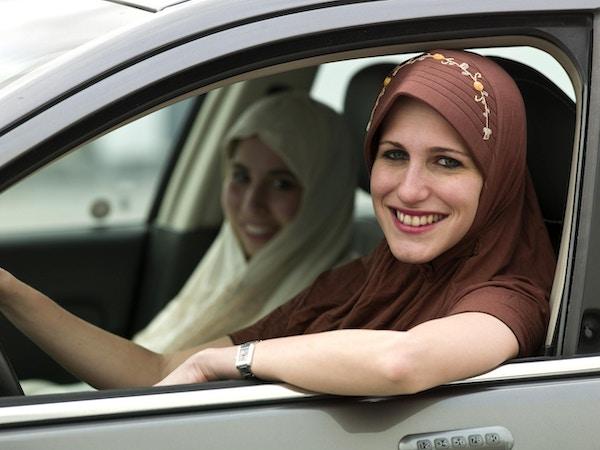 To vakre unge muslimske jenter i en bil i Teheran.