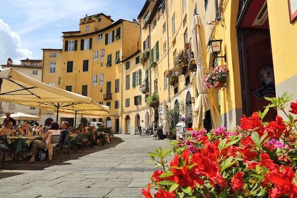 Mennesker som sitter på et spisested på et torg i Lucca, Italia.