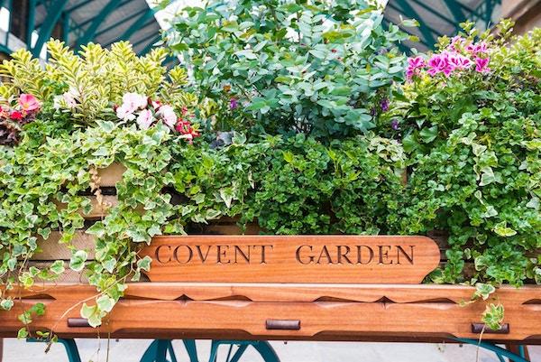 LONDON, Storbritannia - 20. juli 2018: Blomsterfylt vogn ved Londons berømte gamle blomstermarked, Covent Garden.