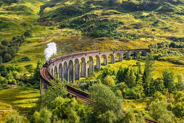 Glenfinnan Railway Viaduct i Skottland med damptog som passerer.