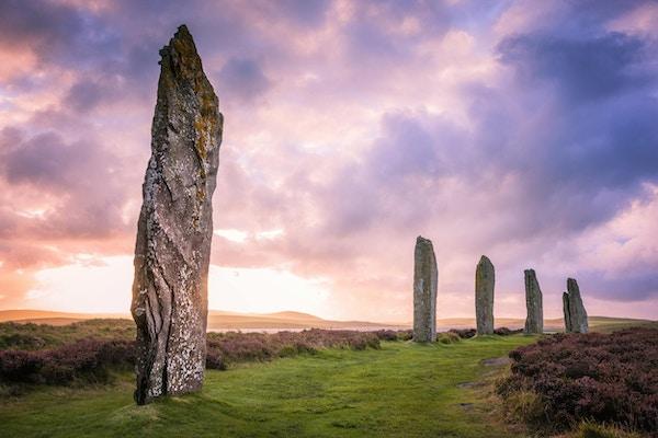 De eldgamle steinene fra Ring of Brodgar på Orknøyene utenfor nordkysten av Skottland, om kvelden like ved solnedgang.