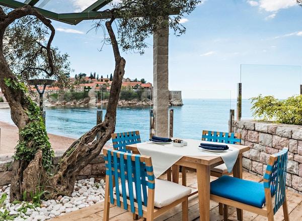 Bord på restaurant ved sjøen med vakker utsikt over øya Saint Stephen i Montenegro