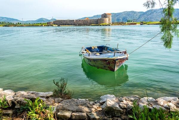 Båt med Ali Pasha slott i bakgrunnen i Butrint, Albania