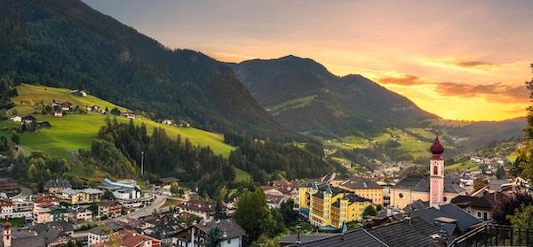 Solnedgang over Ortisei St. Ulrich Urtijei-landsbyen, fjellene i Dolomittene.