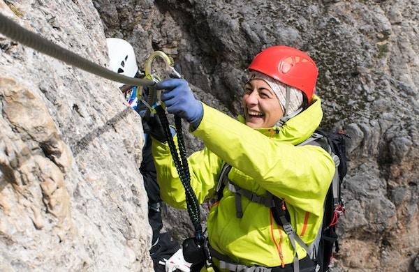 Ung kvinnelig fjellklatrer på en Via Ferrata i Dolomittene i Alta Badia.