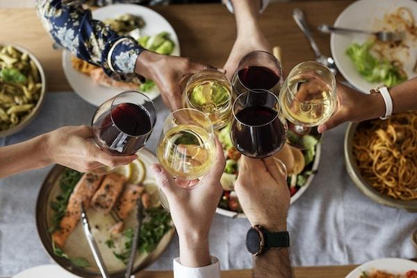 Venner spiser italiensk mat og drikker vin sammen.