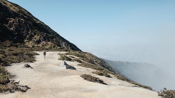 Ung kvinne som går rundt Kawah Ijen vulkankrater. Populært reisemål i Indonesia.