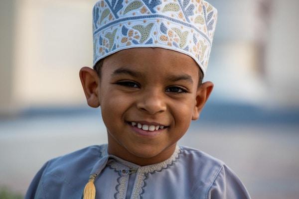 Liten Omani-gutt som smiler og koser seg i parken