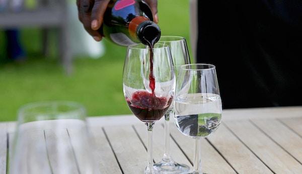 Servitør som heller rødvin i et glass for vinsmaking. Et glass vann står også på bordet.